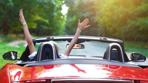 Marketing Review - rear view of lady in red car with hands in the air