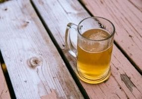 looking down onto a glass of beer on a wooden table
